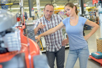Man pointing to mower, woman looking skeptical
