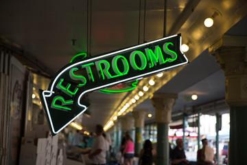 green neon restrooms sign