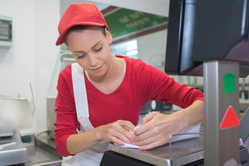 happy saleswoman writing note at a counter in butchers shop