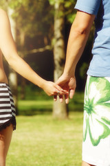 View of couple holding hands in a park in summer