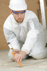 worker chipping at floor tiles