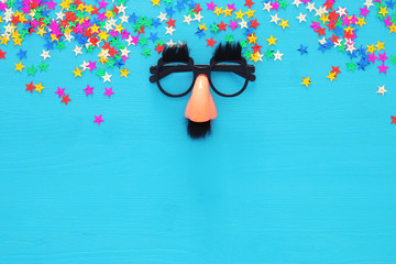 Carnival celebration concept with funny mustache glasses. Top view.