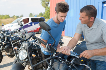 handsome young man is buying a motorbike