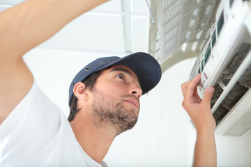 young man cleaning air conditioning system