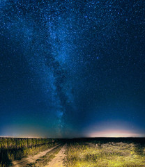 Night Starry Sky Above Country Road In Countryside And Green Field