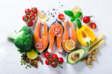 Uncooked salmon fish fillet with aromatic herbs, onion, avocado, broccoli, pepper bell, vegetables on white background, top view. Ingredients for cooking.