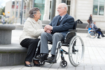 senior on wheelchair with loving wife next to him