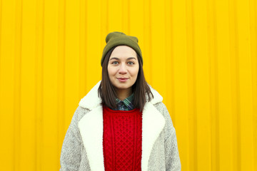 Millenial girl im fashionable clothes having a good time, making funny faces near bright yellow urban wall.