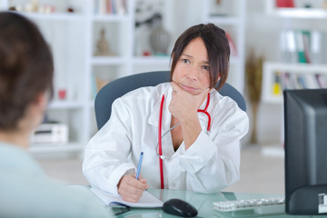 female doctor listening to her patientin office