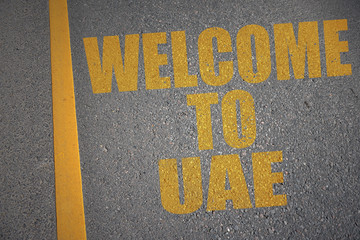 asphalt road with text welcome to uae near yellow line. concept