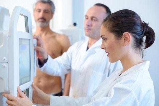 female doctor scanning male torso