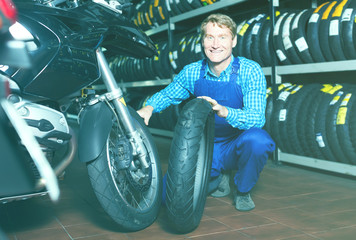 Mature happy mechanic holding new tyre for motorcycle