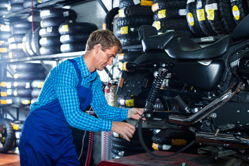 mechanic examining motorcycle