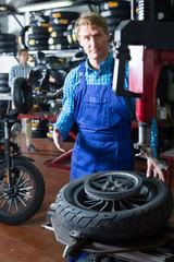 mechanic with bike wheel in workshop .