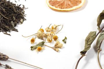 чай сухой лежит на белом столе рядом лежат травы