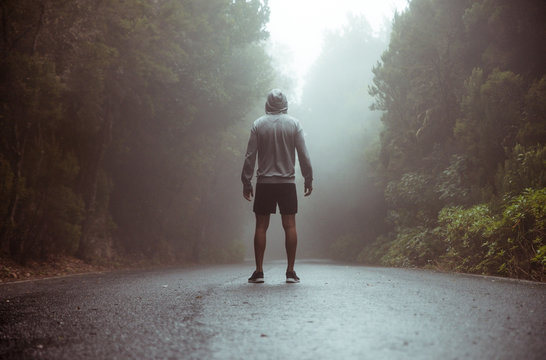 Calm jogger standing on the middle of the road