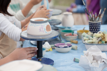 painting ceramics - children painting ceramic dishes