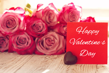 Blank red paper card for Valentines wiht pink roses on dackground.