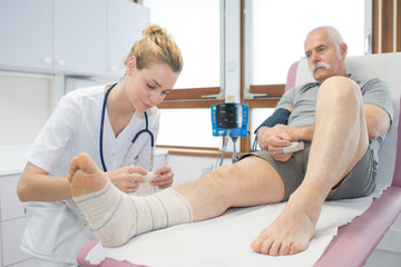 doctor bandaging seniors patients leg in hospital