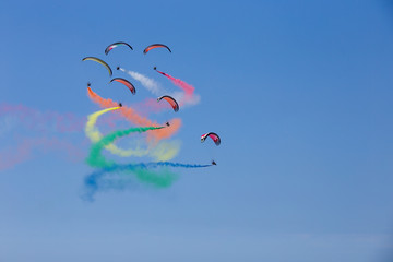 Powered parachutes - multicolored paratroopers during aircraft exhibition with trail of italian flag colors over Grado beach, Italy.