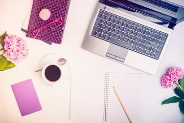 Workspace with laptop, notebook, sketchbook, glasses, cup of coffee and wisteria flowers on white background. Top view feminine office table desk. Freelancer working place.