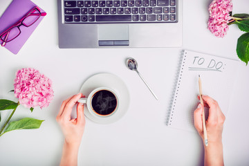 Day Planning - female hands with cup of coffee and pencil write To do list on the white working office desk with laptop, notebook, glasses, and wisteria flowers. Freelance.