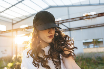 Close view of young woman hip-hop dancer dancing in an abandoned building with sun rays and lens flare