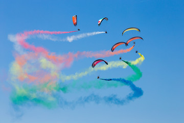 Powered parachutes Air show - multicolored Paratroopers in the sky, aircraft exhibition with trail of italian flag colors over Grado beach, Italy.