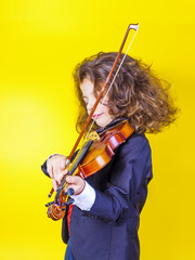 The long-haired seven-year-old boy played the violin. Musical education. Inspiration.