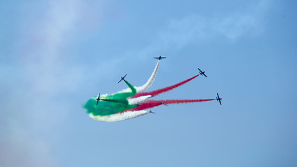 Airshow performance of Frecce Tricolori (Tricolour Arrows) with trail of italian flag colors over Grado beach, Italy.