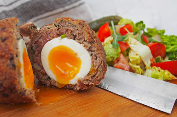 "Traditional ""Scotch egg"" on a wooden plate. Scotch eggs and salad"