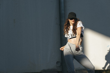 Young woman hip-hop dancer dancing in an abandoned building between lights and shadows