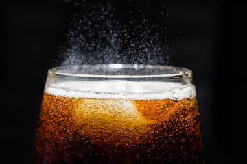 A glass of cola beverage with a salt. On a black background.