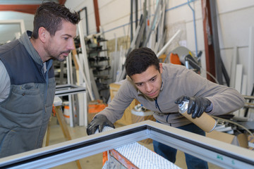 apprentice glazier and mentor in factory workshop
