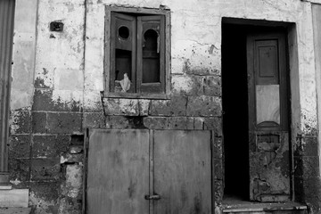 Ruined and Broken Facade With an Open  Door and a Window With a Broken Glass