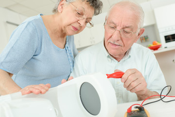 elderly couple fixing coffee maker