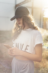 Young woman chatting by mobile phone wearing a baseball cap in an abandoned building and lens flare