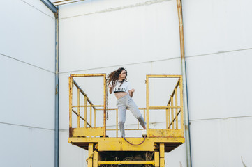 Young woman hip-hop dancer dancing at the top of an abandoned yellow crane