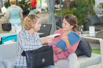 Women talking, holding bag and clipboard
