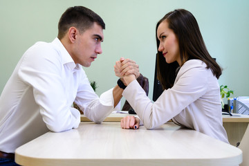 Man and woman in office clothes struggling on his hands over the Desk in the office
