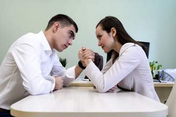 Man and woman in office clothes wrestling on hand at the Desk in the office