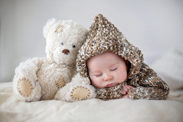 Little baby boy , sleeping at home with soft teddy bear toys
