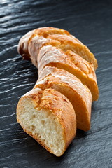 Fresh baguette bread vertical close up shot on the dark background