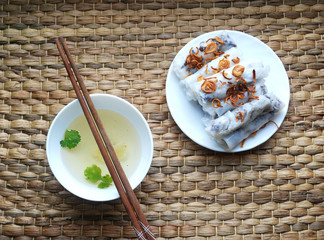 Banh cuon-vietnamese steamed rice rolls with minced meat inside accompanied by bowl of fish sauce.