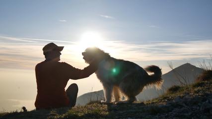 Uomo con il cane al tramonto