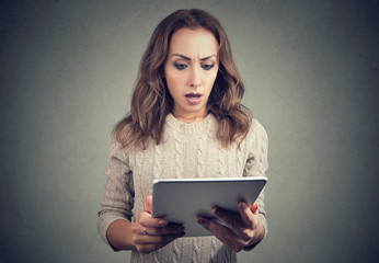 Terrified young woman watching tablet