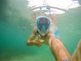 Underwater selfie with a man snorkeling in the blue sea