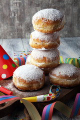 German donuts with jam and icing sugar. Carnival powdered sugar raised donuts with paper streamers.
