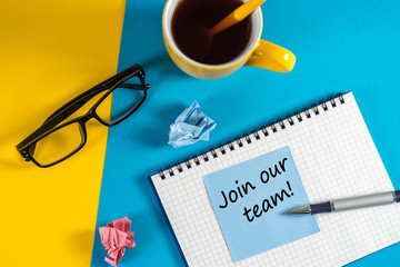 Join our team - message at blue note near morning coffee cup at blue and yellow background. Hiring and new job concept