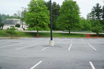 empty parking lot with spring green trees outside